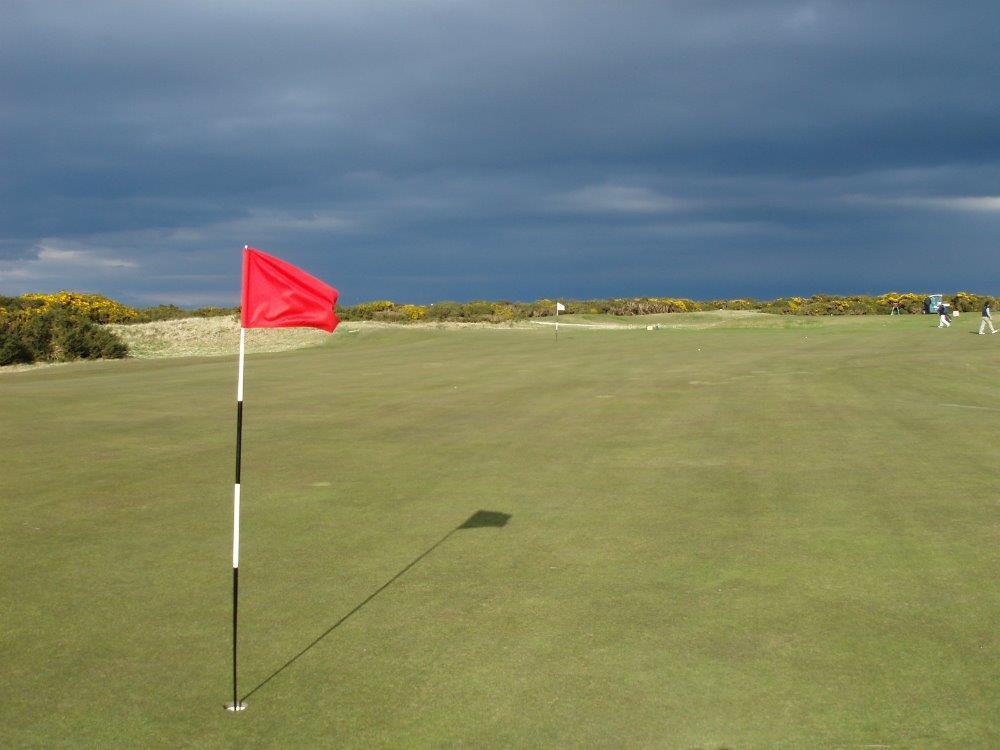 Markierungsfahne und Golfgrün in der Sonne auf dem Old Course Golfkurs in St.Andrews, Schottland