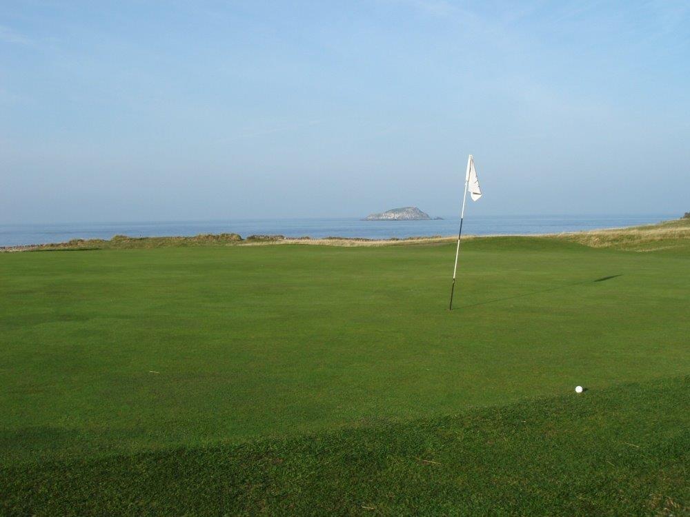 Golfgrün mit Markierungsfahne und Meeresausblick auf dem North Berwick Golfkurs in der Nähe von Edinburgh, Schottland