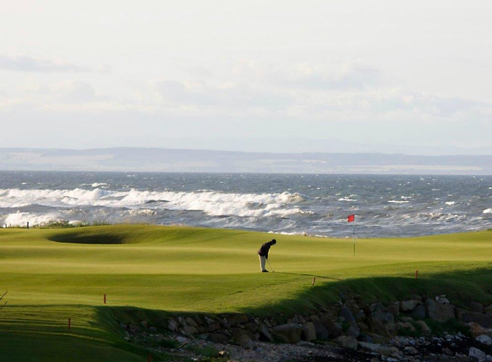 Golfgrün mit Golfspieler, Markierungsfahne und Meeresblick auf dem Kingsbarns Golfkurs in St.Andrews, Schottland