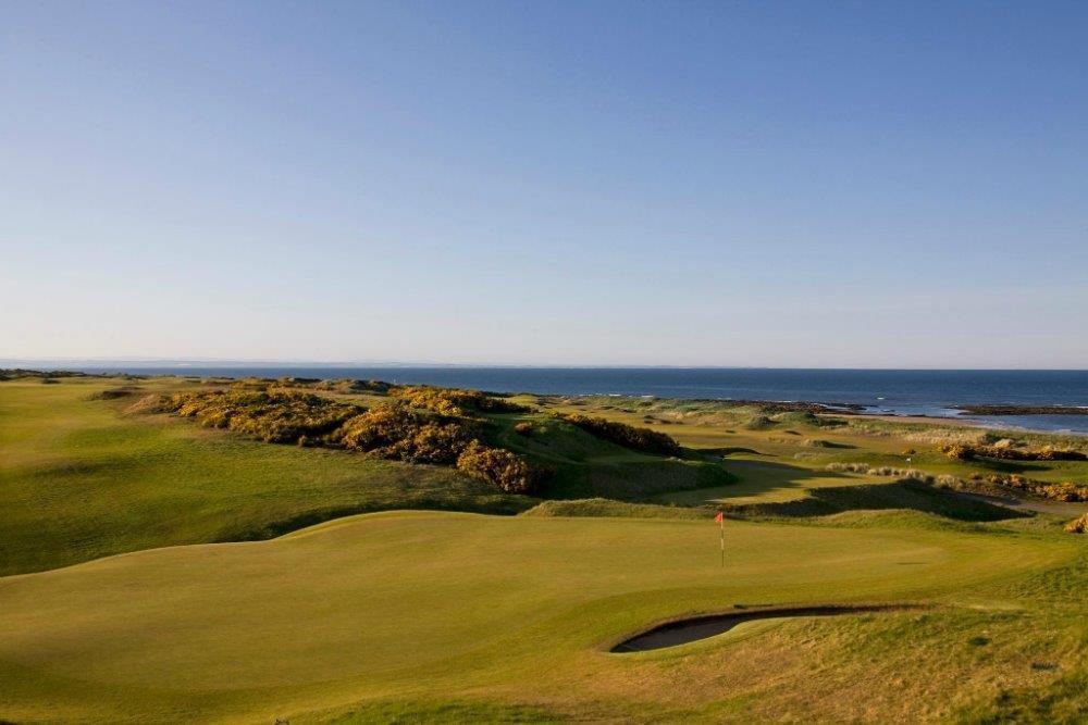 Golfgrün mit Markierungsfahne und Meeresblick in der Sonne in Kingsbarns, Schottland