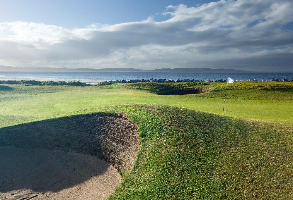 Golfgrün mit Bunker und Meeresblick auf dem Nairn Golfkurs in den Highlands, Schottland
