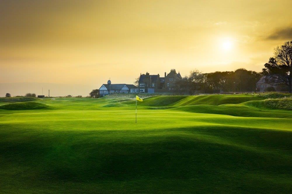 Golfgrün mit Markierungsfahne und Club Haus im Sonnenuntergang in der Nähe von Inverness, Highlands, Schottland