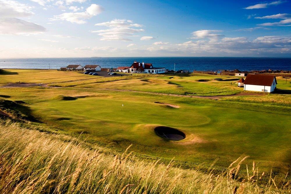 Fairway mit Club Haus und Meeresblick auf dem Dunbar Golfkurs in der Nähe von Edinburgh, Schottland