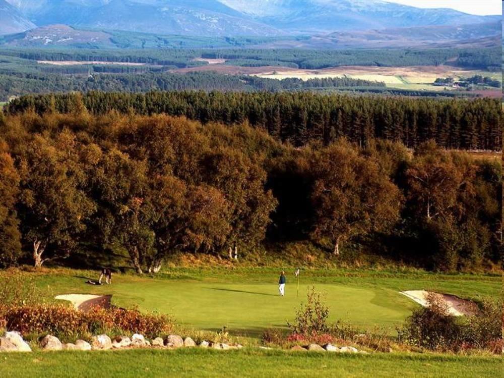 Golfgrün mit Golfspieler und Ausblick auf die Berge auf dem Kingussie Golfkurs in den Highlands, Schottland