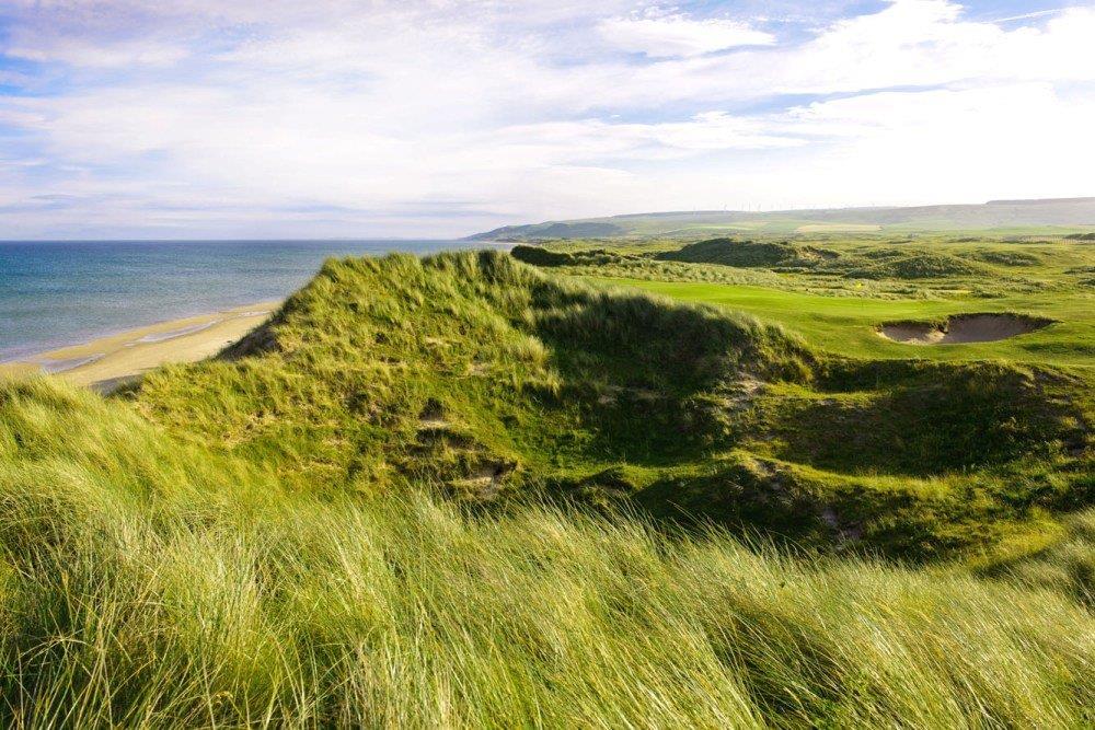 Golfgrün mit Bunker, Strand und Meeresblick auf dem Machrihanish Dunes Golfkurs in Campbeltown, Schottland