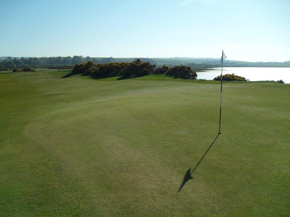 Golfgrün mit Markierungsfahne und Meeresausblick auf dem Eden Course Golfkurs in St.Andrews, Schottland