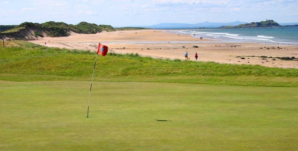 Golfgrün mit Markierungsfahne, Strand und Meeresblick auf dem North Berwick Golfkurs in der Nähe von Edinburgh, Schottland