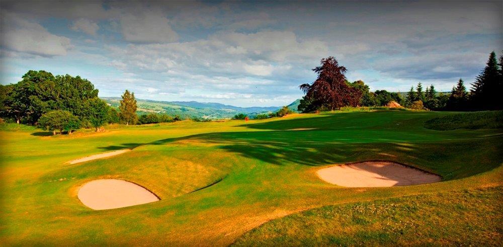 Golfgrün mit Bunker und Ausblick auf die Berge auf dem Pitlochry Golfkurs in der Nähe von St.Andrews, Schottland