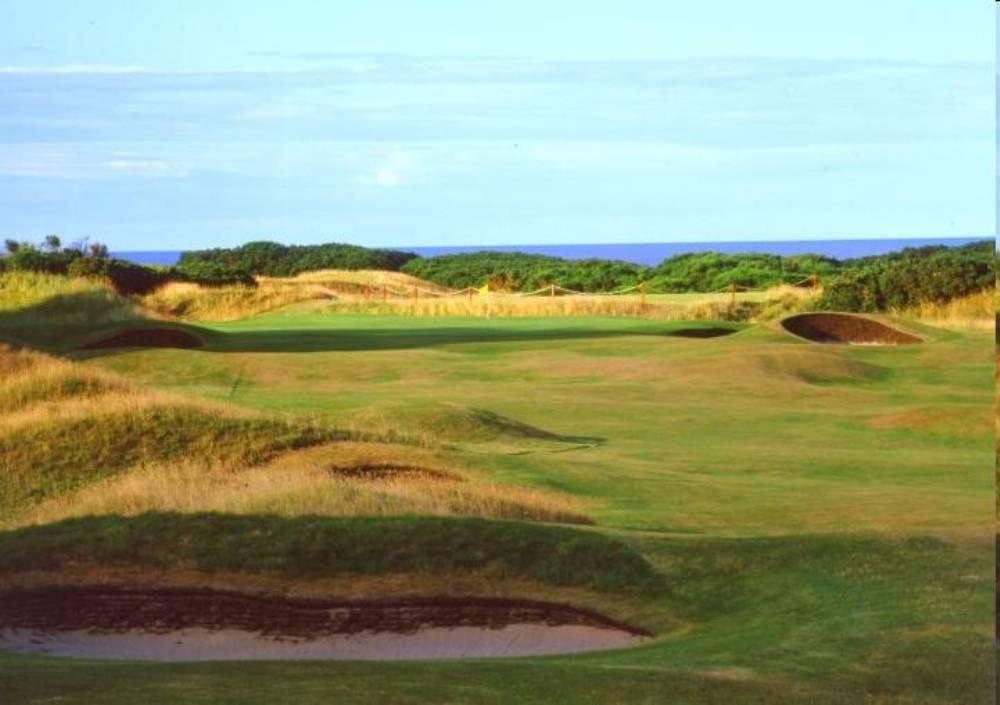 Golfgrün mit Bunker und Meeresblick auf dem Royal Dornoch Championship Golfkurs in den Highlands, Schottland