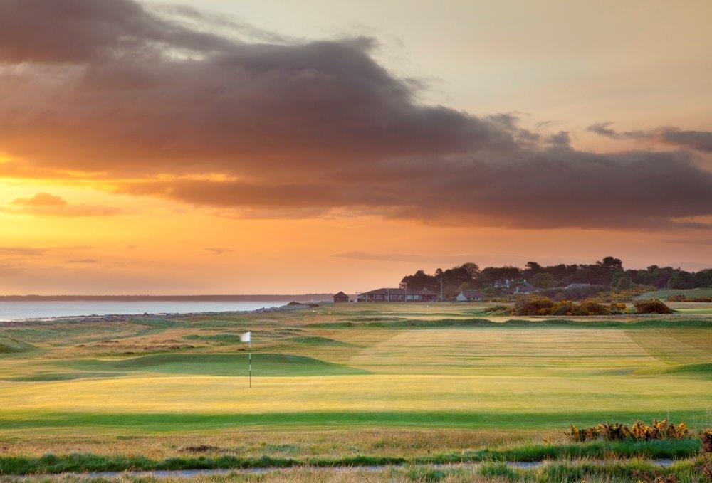 Fairways mit Markierungsfahne, Club Haus und Meeresausblick im Sonnenuntergang in Inverness, Highlands, Schottland