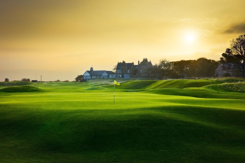 Golfgrün mit Markierungsfahne und Club Haus auf dem Royal Dornoch Championship Golfkurs in den Highlands, Schottland