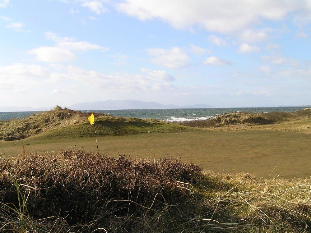 Golfgrüns mit Markierungsfahne und Meeresausblick auf dem Western Gailes Golfkurs in der Nähe von Glasgow, Schottland