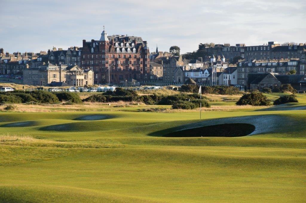 Golfgrün mit Bunker und Blick auf die Stadt auf dem Old Course Golfplatz in St Andrews, Schottland