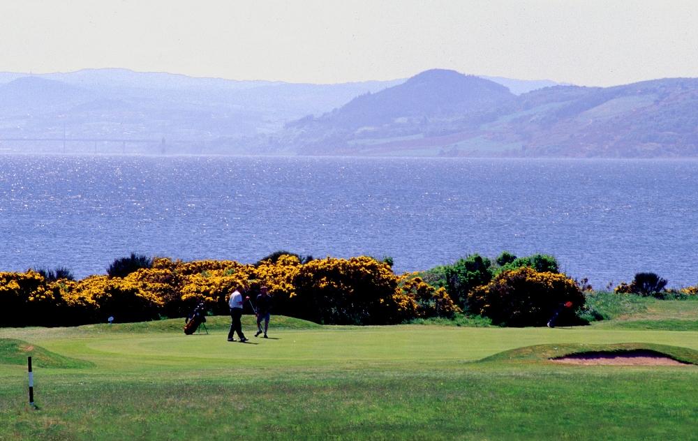 Golfgrün mit Golfspieler, Meer und Blick auf die Berge auf dem Fortrose und Rosemarkie Golfkurs in den Highlands, Schottland