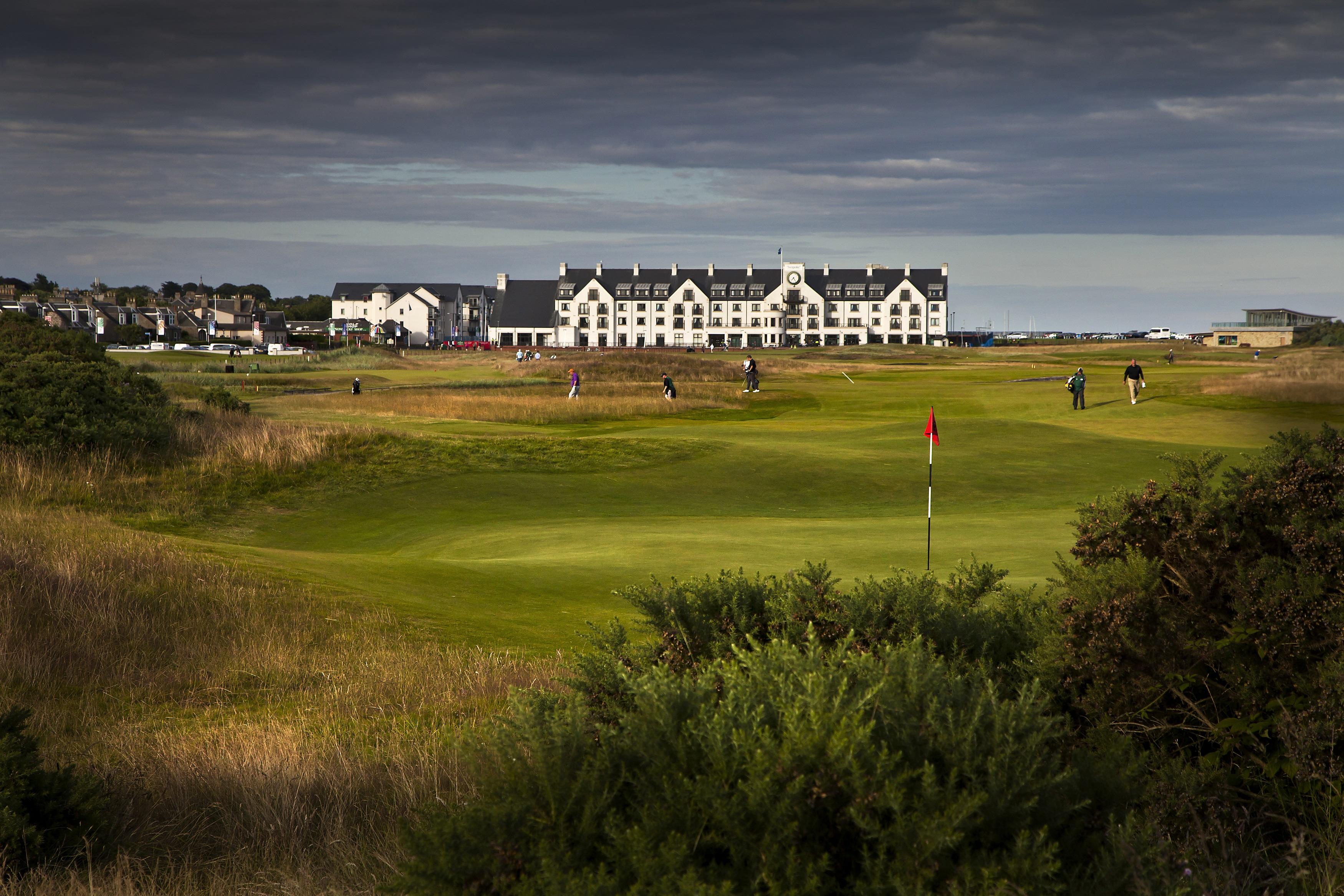 Golfgrün mit Golfspieler und Club Haus auf dem Carnoustie Golfplatz in Schottland