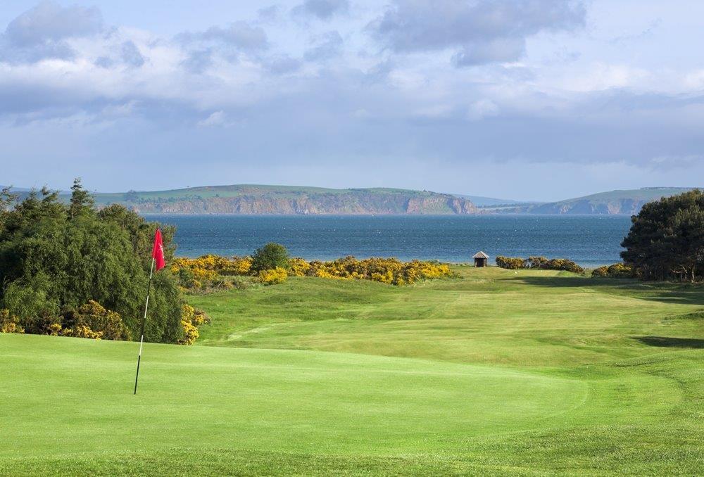 Golfgrün mit Markierungsfahne und Meeresausblick auf dem Nairn Golfkurs in Inverness, Highlands, Schottland