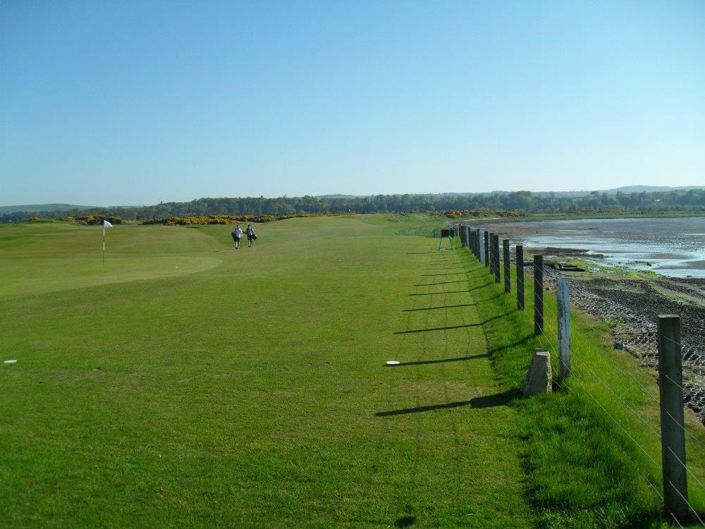 Golfgrün mit Golfspieler und Strand und Meeresausblick auf dem Eden Course Golfkurs in St.Andrews, Schottland