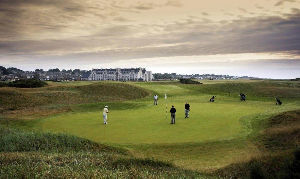 Golfgrün mit Golfspieler und Club Haus auf dem Carnoustie Golfplatz in der Nähe von St Andrews, Schottland