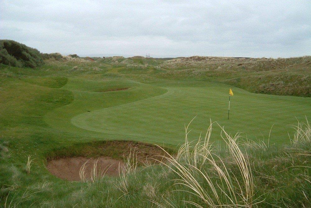 Golfgrüns mit Bunker und Markierungsfahne auf dem Western Gailes Golfkurs in der Nähe von Glasgow, Schottland