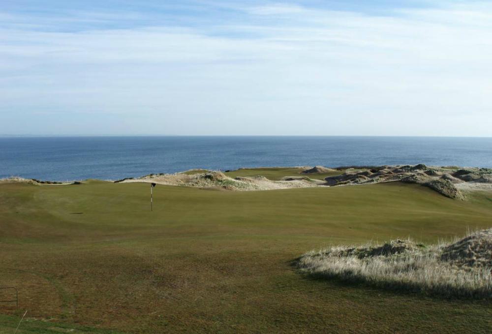 Golfgrün mit Markierungsfahne und Meer auf dem Castle Course Golfkurs in St.Andrews, Schottland