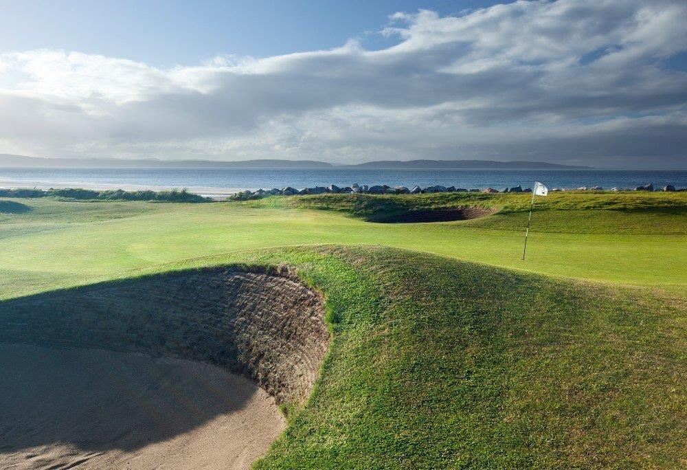 Golfgrün mit Bunker, Markierungsfahne und Meeresausblick auf dem Nairn Golfkurs in Inverness, Highlands, Schottland