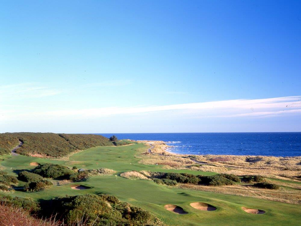 Golfgrün mit  Bunker und Meeresausblick auf dem Royal Dornoch Golfkurs in der Nähe von Inverness, Highlands, Schottland