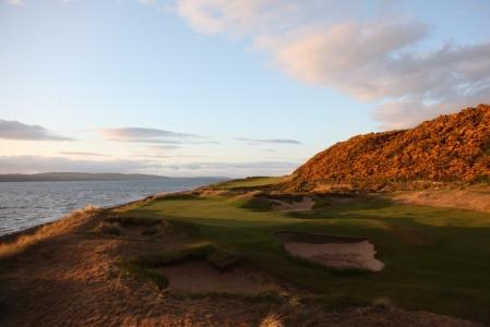 Golfgrün mit Bunker und  Meeresblick auf dem Castle Stuart Golfkurs in Dornoch, Schottland