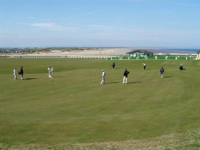 Golfgrün mit Golfspieler und Caddy, Strand und Meeresblick auf dem Old Course Golfkurs in St.Andrews, Schottland
