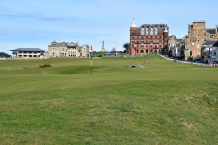 Golfgrün mit Markierungsfahne und Club Haus auf dem Old Course Golfplatz in St Andrews, Schottland