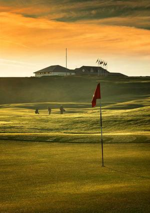 Golfgrün mit Markierungsfahne, Golfspieler und Club Haus auf dem Crail Balcomie Golfkurs in St.Andrews, Schottland