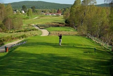 Fairway mit Golfspieler, Club Haus und Blick auf die Berge auf dem Boat of Garten Golfkurs in den Highlands, Schottland