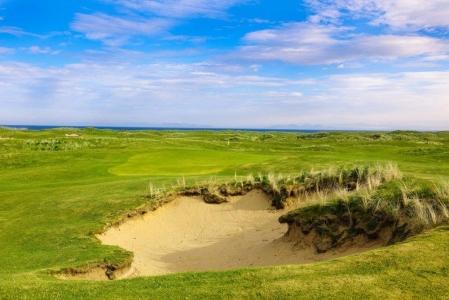 Golfgrün mit Bunker und Meeresblick auf dem Machrihanish Dunes Golfkurs in Campbeltown, Schottland