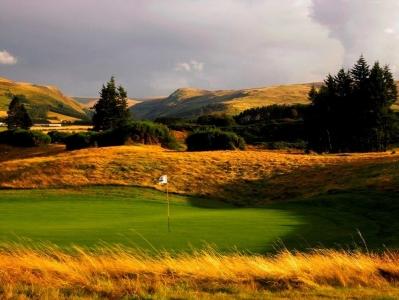 Golfgrün mit Markierungsfahne und Blick auf die Berge auf dem Gleneagles King´s Golfkurs in der Nähe von St .Andrews, Schottland