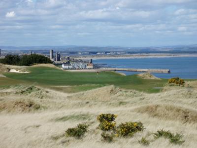 Golfgrün mit Markierungsfahne und Blick auf St.Andrews auf dem Castle Course Golfplatz  in Schottland
