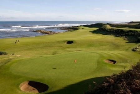 Fairways mit Golfspieler und Meeresblick in der Sonne in Kingsbarns, Schottland