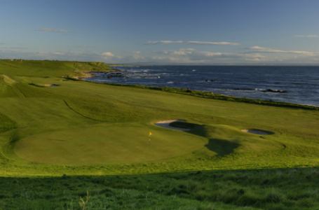 Fairway mit Meeresblick im Sonnenuntergang auf dem Crail Balcomie Golfkurs in St.Andrews, Schottland