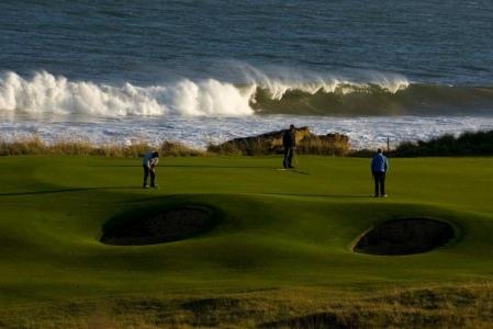 Golfgrün mit Bunker, Golfspieler und Meeresblick auf dem Royal Dornoch Golfkurs in der Nähe von Inverness, Highlands, Schottland
