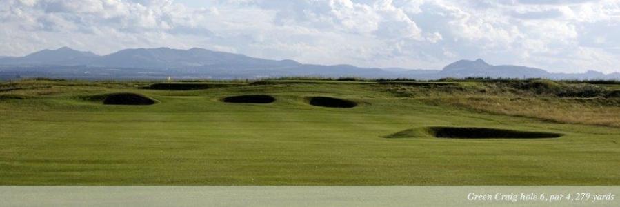 Golfgrün mit Bunker und Ausblick auf die Berge auf dem Kilspindie Golfkurs in Edinburgh, Schottland