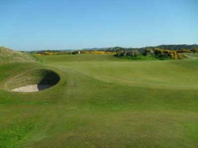 Golfgrün mit Bunker und Markierungsfahne auf dem Eden Course Golfkurs in St.Andrews, Schottland