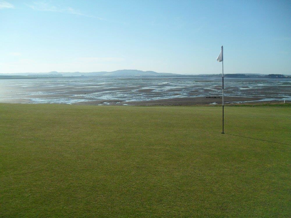 Golfgrün mit Markierungsfahne und Meeresausblick auf dem Eden Course Golfkurs in St,Andrews, Schottland