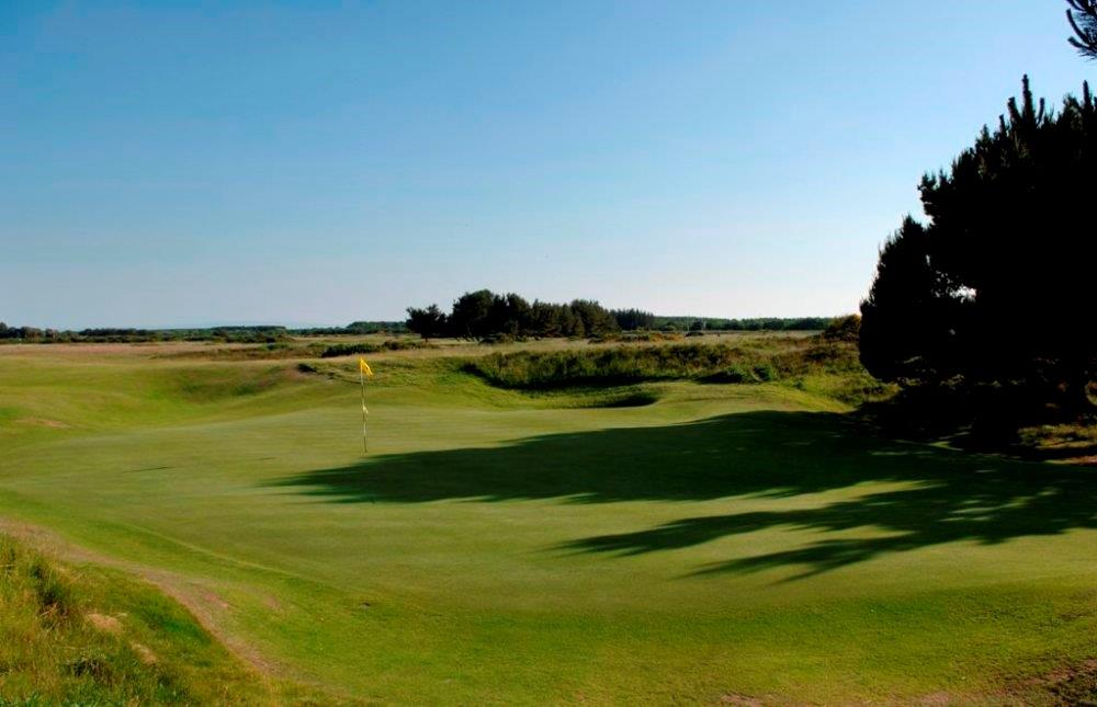Golfgrün mit Markierungsfahne auf dem Glasgow Gailes Golfkurs in Schottland