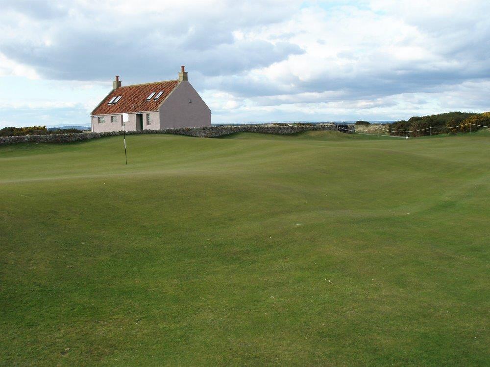 Golfgrün mit Markierungsfahne und Club Haus auf dem Eden Course Golfkurs in St.Andrews, Schottland
